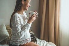 A mulher gravida atrativa bebe o chá na cama Chá bebendo que olha através de uma janela em casa Últimos meses da gravidez imagem de stock royalty free