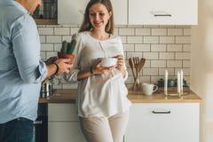 A mulher gravida atrativa nova está estando na cozinha, inclinando-se na tabela, guardando a bacia em suas mãos O homem está próx Imagens de Stock Royalty Free