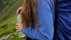 A mulher gravida bebe a água na montanha Close-up E filme