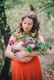 Mulher gravida bonita com as flores na cesta Imagem de Stock