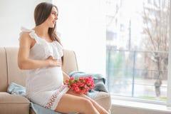 Mulher gravida bonita com o ramalhete das flores Fotografia de Stock
