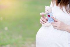 Mulher gravida bonita e feliz no jardim com boneca Imagem de Stock Royalty Free