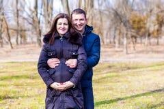 Mulher gravida bonita e seu marido considerável que abraçam a barriga fotografia de stock