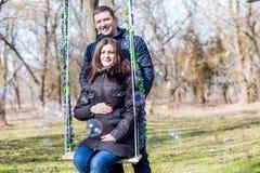 Mulher gravida bonita e seu marido considerável que abraçam a barriga no balanço fotografia de stock