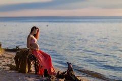 Mulher gravida bonita na praia no por do sol Fotos de Stock