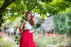 Mulher gravida bonita nova em um balanço decorado com rosas vermelhas Foto de Stock Royalty Free