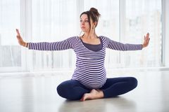 Mulher gravida bonita nova que faz o asana Padmasana da ioga - os lótus levantam em casa foto de stock