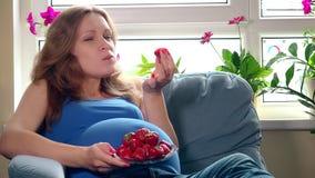 Mulher gravida bonita que come morangos e que sorri olhando a câmera filme