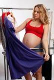 Mulher gravida bonita que escolhe que desgastar imagem de stock royalty free