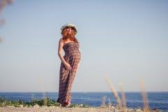 Mulher gravida bonita que relaxa perto do mar Fotos de Stock Royalty Free