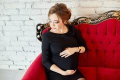 Mulher gravida bonita que senta-se em um sofá vermelho Na antecipação Imagens de Stock