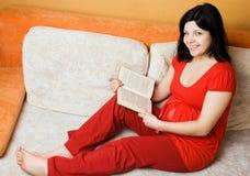 Mulher gravida bonita que senta-se no sofá Foto de Stock Royalty Free
