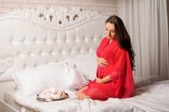 A mulher gravida bonita vestiu-se no négligé elegante que senta-se na cama Foto de Stock Royalty Free