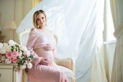 A mulher gravida bonito que sentam-se em cortinas billowing próximas da cadeira e os abraços incham-se com amor imagens de stock