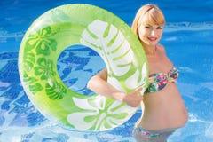 Mulher gravida com anel de borracha verde na natação Imagem de Stock Royalty Free