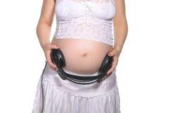 Mulher gravida com auscultadores foto de stock
