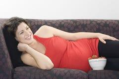 Mulher gravida com a bacia de morangos que relaxam no sofá Fotos de Stock