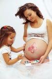 Mulher gravida com a barriga bonito da pintura da filha Imagem de Stock