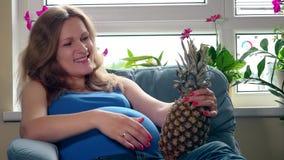 Mulher gravida com a barriga grande que guarda o fruto do ananás do abacaxi que senta-se no sofá video estoque
