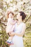 Mulher gravida com a filha no parque que abraça o beijo Imagens de Stock