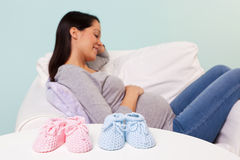 Mulher gravida com montantes do bebê em uma tabela imagens de stock