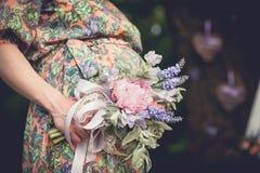 A mulher gravida com o ramalhete brilhante do verão das flores guarda as mãos na barriga em um dia ensolarado fora Gravidez, pate fotos de stock royalty free