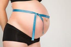 Mulher gravida com o ruller que levanta no estúdio imagens de stock