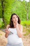 Mulher gravida com PC da tabuleta foto de stock