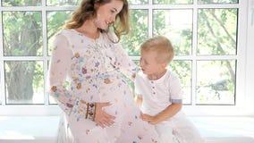 Mulher gravida com pouco filho no peitoril da janela filme
