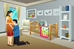 Mulher gravida com seu marido na sala do berçário Imagens de Stock