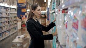 A mulher gravida compra os tecidos no supermercado, retrato da mãe feliz nova na loja Imagem de Stock