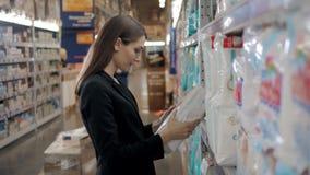 A mulher gravida compra os tecidos no supermercado, retrato da mãe feliz nova na loja Foto de Stock Royalty Free