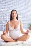 Mulher gravida concentrada que senta-se na posição dos lótus sobre a cama imagens de stock royalty free