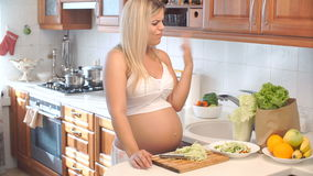 A mulher gravida corta a couve na placa de madeira e corta seu dedo vídeos de arquivo