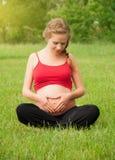 A mulher gravida é de descanso e de relaxamento na natureza Foto de Stock Royalty Free