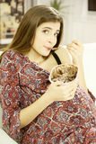 Mulher gravida de sorriso bonito que come o gelado de chocolate em casa que olha a câmera Imagem de Stock Royalty Free
