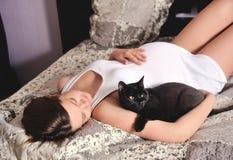 Mulher gravida de sorriso com gato em casa. Imagens de Stock