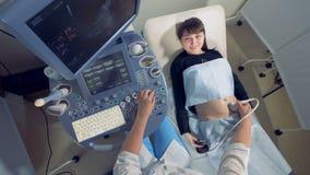 A mulher gravida de sorriso está observando seu próprio processo do ultrassom filme
