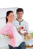 Mulher gravida de sorriso que come morangos em casa Fotografia de Stock