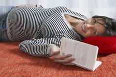 Mulher gravida de sorriso que encontra-se no assoalho com livro Fotografia de Stock Royalty Free