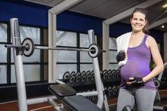 Mulher gravida de sorriso que está ao lado do banco foto de stock