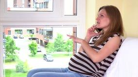 Mulher gravida de sorriso que fala no telefone vídeos de arquivo