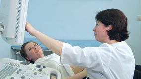 A mulher gravida de sorriso que olha o ultrassom resulta com doutor Imagens de Stock Royalty Free