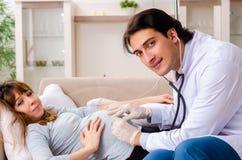 A mulher gravida de visita do doutor considerável novo em casa fotos de stock royalty free