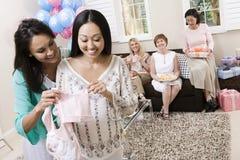 Mulher gravida e amigo que guardaram a roupa do bebê imagens de stock