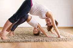 Mulher gravida e exercício pequeno da ioga da filha Foto de Stock