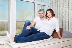 Mulher gravida e homem felizes nas calças de brim Fotografia de Stock Royalty Free
