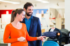 Mulher gravida e homem na loja do bebê imagens de stock