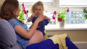 A mulher gravida e a menina bonita da criança que olham o bebê vestem-se filme