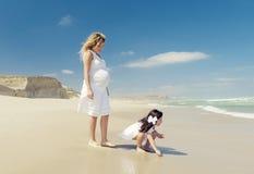 Mulher gravida e sua filha na praia fotos de stock royalty free